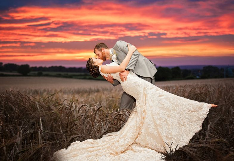 Bride and groom in a wheat field under a dramatic sky