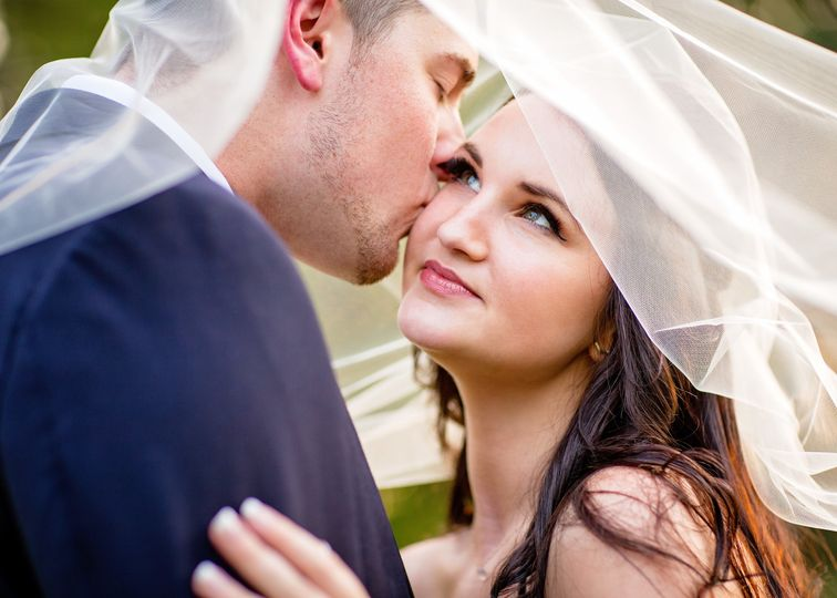 Bride and groom under a veil at Cape Fear Botanical Gardens