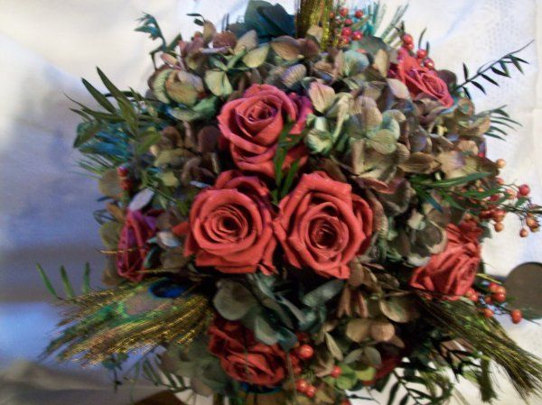 Bordeaux hydrangea, Cranberry roses, pepper berries, peacock feathers, All preserved soft to the...