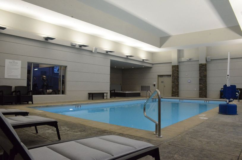 Indoor pool and hot tub with view of exercise room