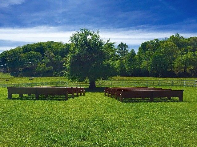 Large restored church pews for an outdoors ceremony