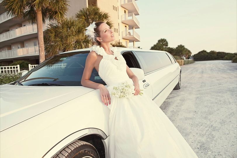 Bride posing with the limo