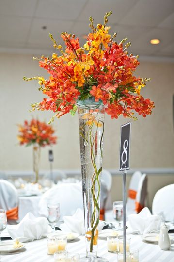 A tall pilsner vase highlights the orange mokara orchids that make theae centerpieces the focal...