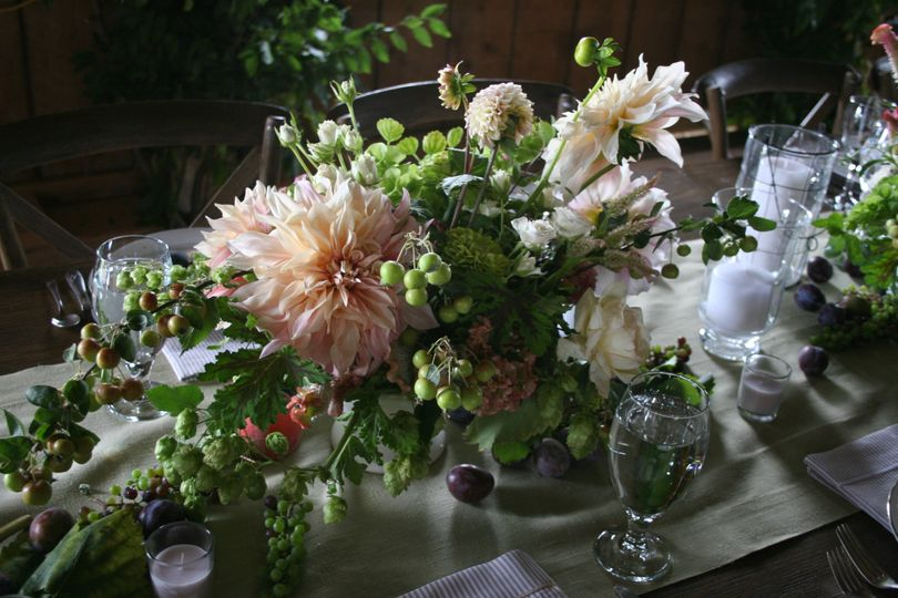 A centerpiece at an elegant barn wedding loaded with dahlias, grapes, crab apples and so much more...