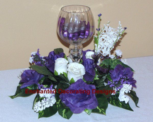 A glass hurricane candle holder sits in the center of an array of open roses and rose buds with...