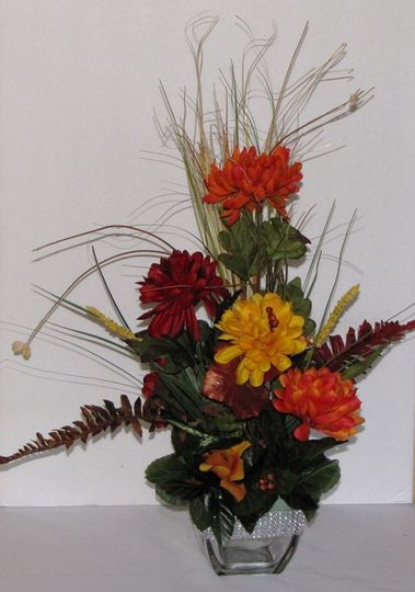 This beautiful soft colored wedding centerpiece were custom made using burnt orange, deep red and...
