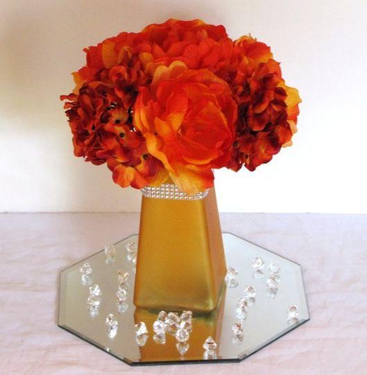 I created this beautiful, silk peony and hydrangea wedding centerpiece. The orange glass vase has a...