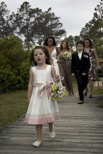 The flower girl leads the way to the sandy ceremony.