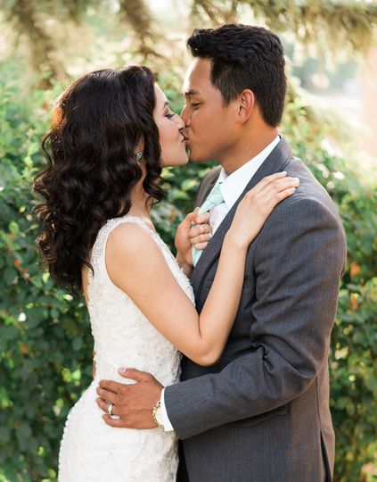 bride and groom kissing for photographer