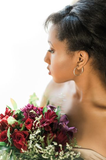 bride looking out the window with a bouquet