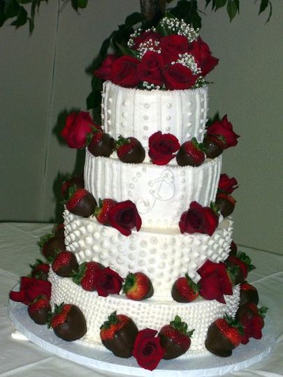 This is a Fresh Strawberry Cake with chocolate covered strawberrys and red roses on a buttercream...