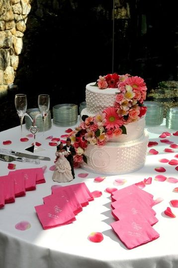 3 tiered white and red velvet cake with buttercream icing and a variety of fresh pink flowers...