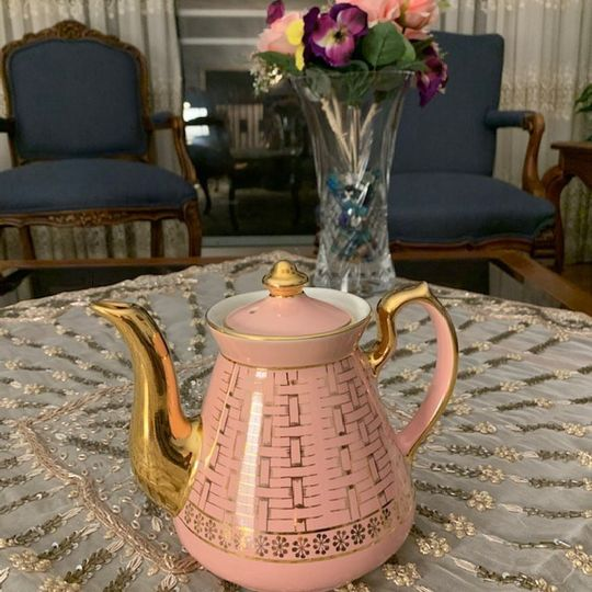 A pink teapot with gold accents