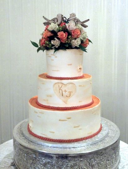 Three layered wedding cake with flowers on top