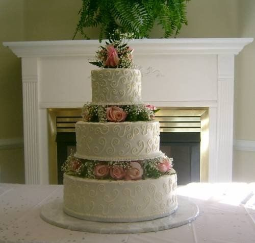 Fresh pink roses, greenery, and baby's breath seperate three delicious double layers covered with...