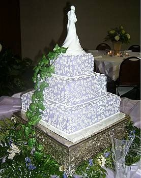 This elegant square 3 tiered cake is covered with pale lilac fondant and swirls of buttercream icing...