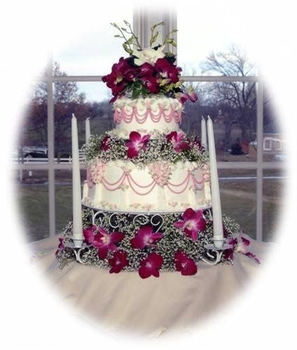 This 2 tiered round cake is covered in buttercream with royal flower accents on a candle holder...