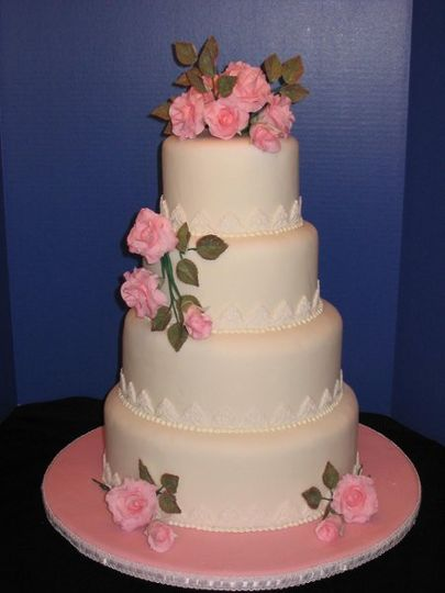 This 4 tiered stacked cake is covered in fondant icing with gumpaste flowers and fondant accents.