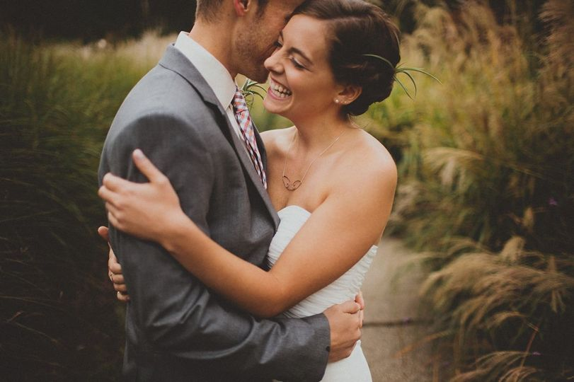 Wedding Couple in front of tall ornamental grasses. Photo credit Ashley Dru Photography.