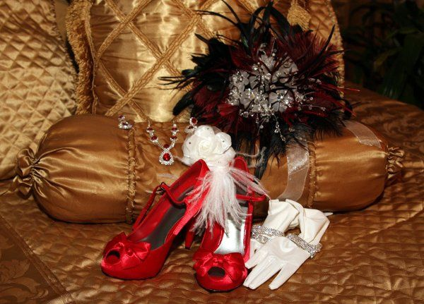 The Brides accessories consisted of Red shoes, a black and red custom bouquet made of feathers and...