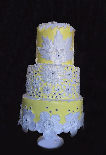White flowers on yellow wedding cake
