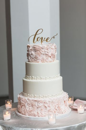 Soft romantic pink ruffled cake with white jewel border on two tiers.