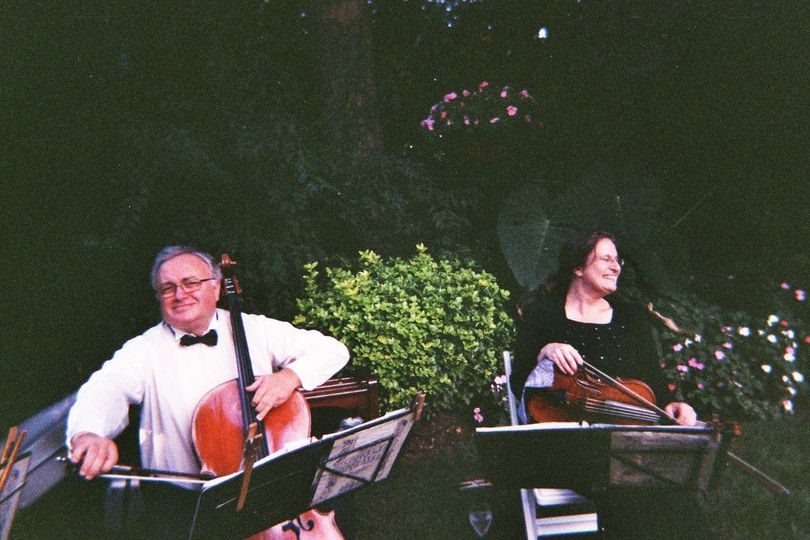 Wedding musicians tuning up and having fun in the garden pre-wedding ceremony at the westbury manor