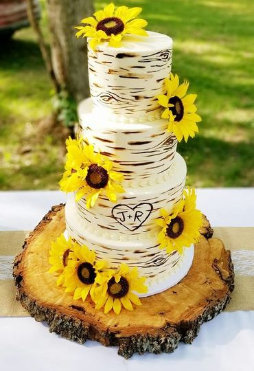 Buttercream rustic wedding cake with silk sunflowers