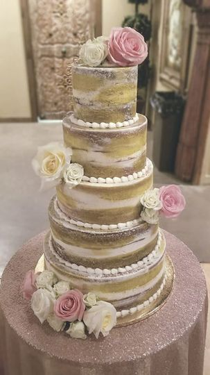 Naked wedding cake with gold brush strokes and fresh flowers