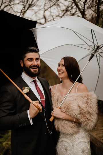 Newlyweds with umbrellas