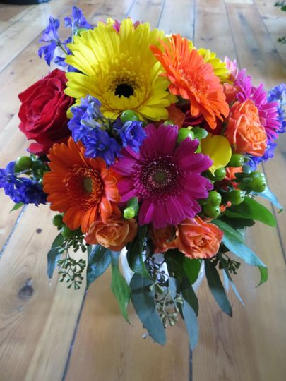 Fun mix of gerbera daisies, green hypericum berries, yellow calla lilies, orange spray roses, seeded...