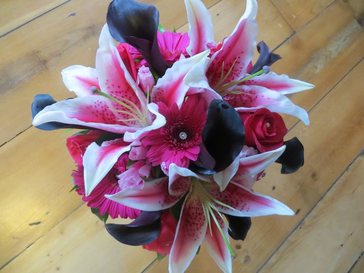Feminine bouquet of stargazer lilies, plum calla lilies, pink roses and gerbera daisies and added...