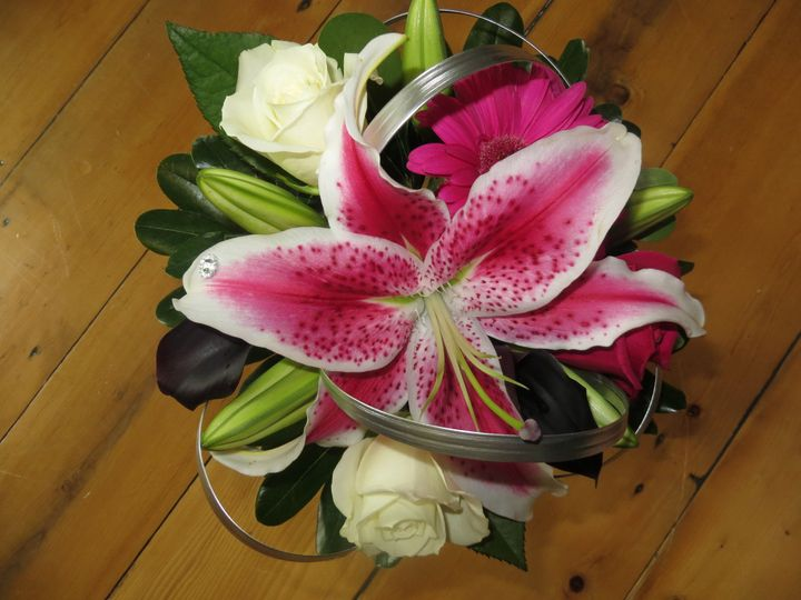 Bouquet with stargazer lilies, escimo roses, plum calla lilies and silver accented lily grass.