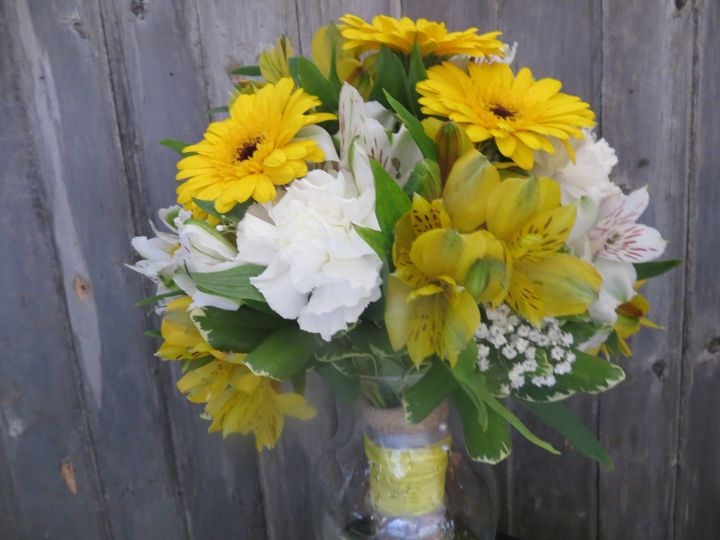 Fun, country bouquet with yellow and white alstromeria lilies, yellow gerberas, white carnations and...