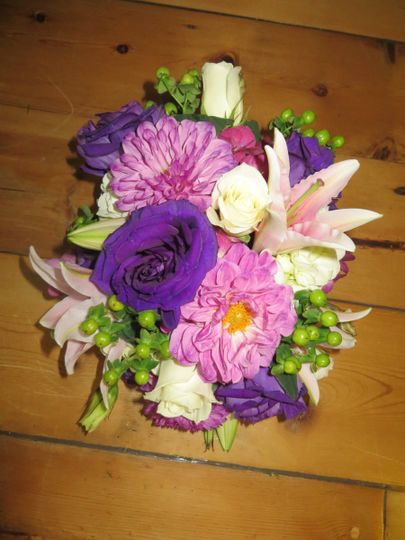 Gorgeous cascading bouquet of lilies, purple lisianthus, escimo roses, green hypericum berries ad...