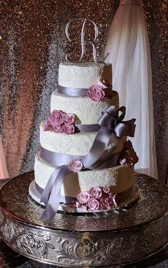 Buttercream frosted cake with edible icing and roses with satin ribbon