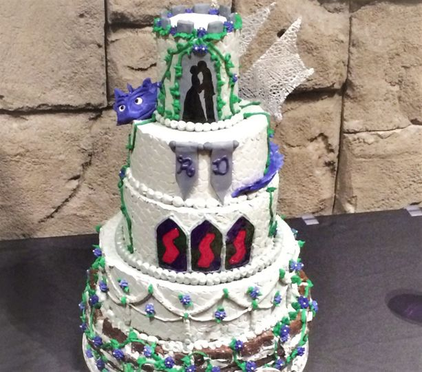Buttercream wedding cake with fondant dragon wrapped around it and brownie stone bottom tier