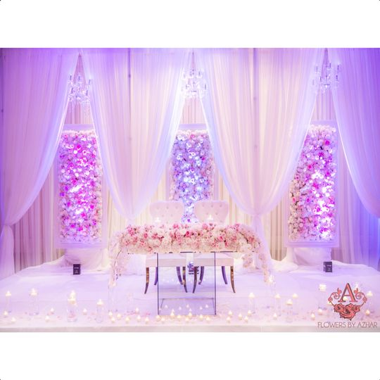 Sweetheart table on riser for the Bride & Groom. We added draping with hanging chandeliers to dress...