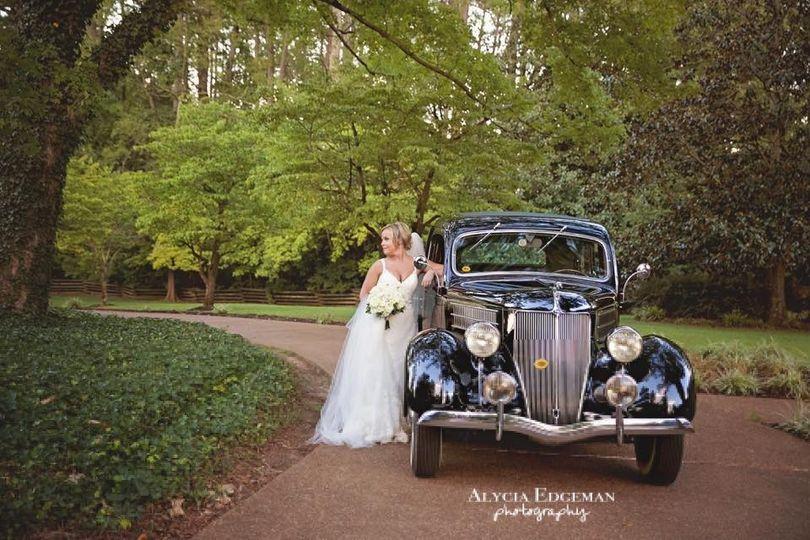 Bridal portrait with wedding getaway car