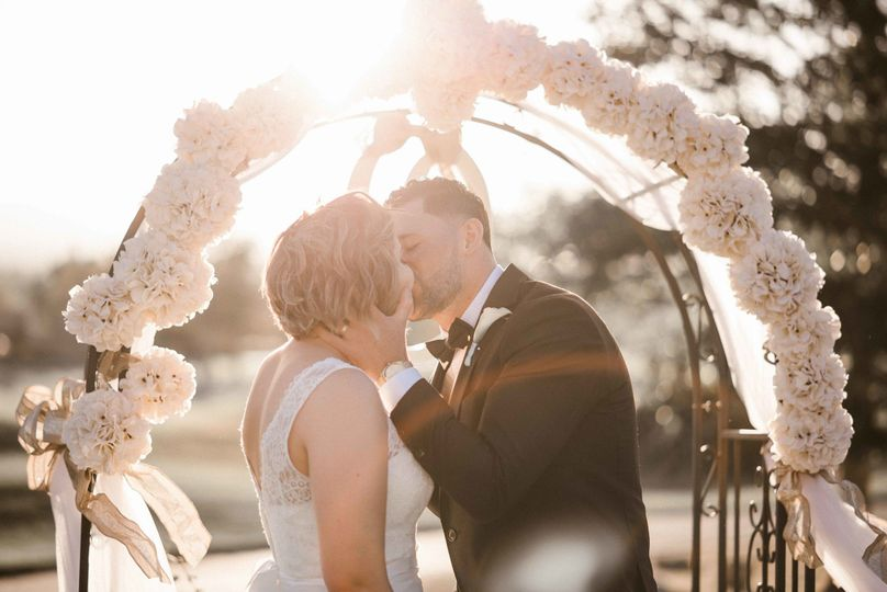 Bride & Groom kissing under ceremony arch during sunset