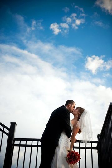 Newlyweds kiss by the rails