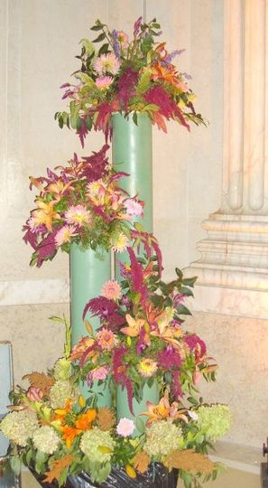 Several different types and colors of lilies and dahlias in mixed tiered arrangements for a large...