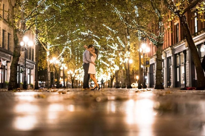couple kissing under lights at night in pioneer sq