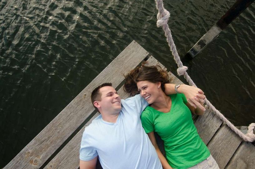 engaged couple laughing on dock