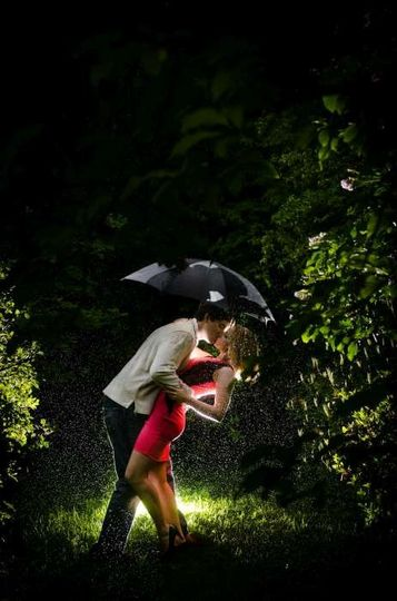engagement photo couple kissing under umbrella in