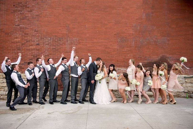 fun bridal party cheers on bride and groom in city