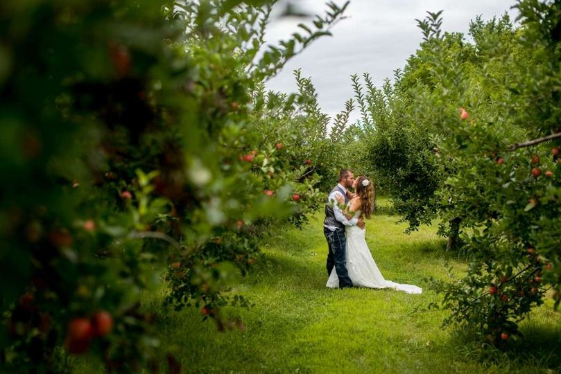 outdoor wedding couple kissing in apple orchard