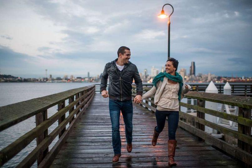 travel loving couple running on alki beach warf