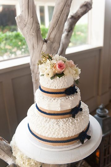 White textured cake with blue ribbons