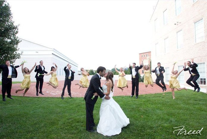 Newlyweds kissing with guests jumping in the background